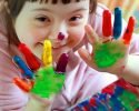 Smiling Downs syndrome child showing her hands covered with paint
