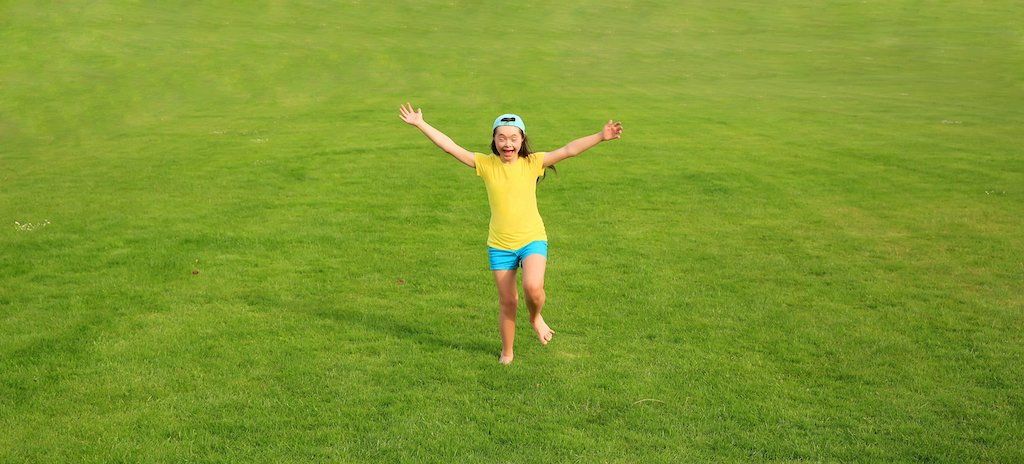 Happy Downs Syndrome girl runs with arms out towards the camera