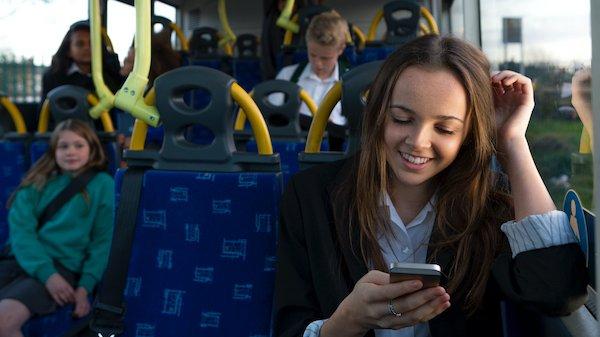 Young Schoolgirl Using Smartphone on Bus